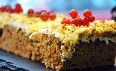 Carrot cake slice with cream cheese and red berries